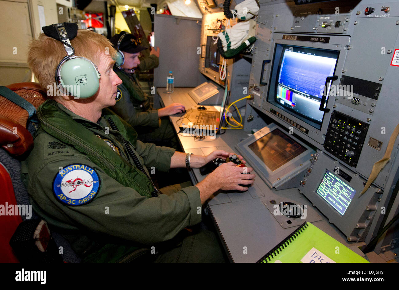 Canberra. 24th Mar, 2014. Royal Australian Air Force Warrant Officer Adam Tucker operates the electro optical camera onboard an AP-3C Orion over the south Indian Ocean as part of the Australian Maritime Safety Authoirty-led search for Malaysia Airlines flight MH370 on March 24, 2014. © Australian Department of Defense/Xinhua/Alamy Live News - Stock Image