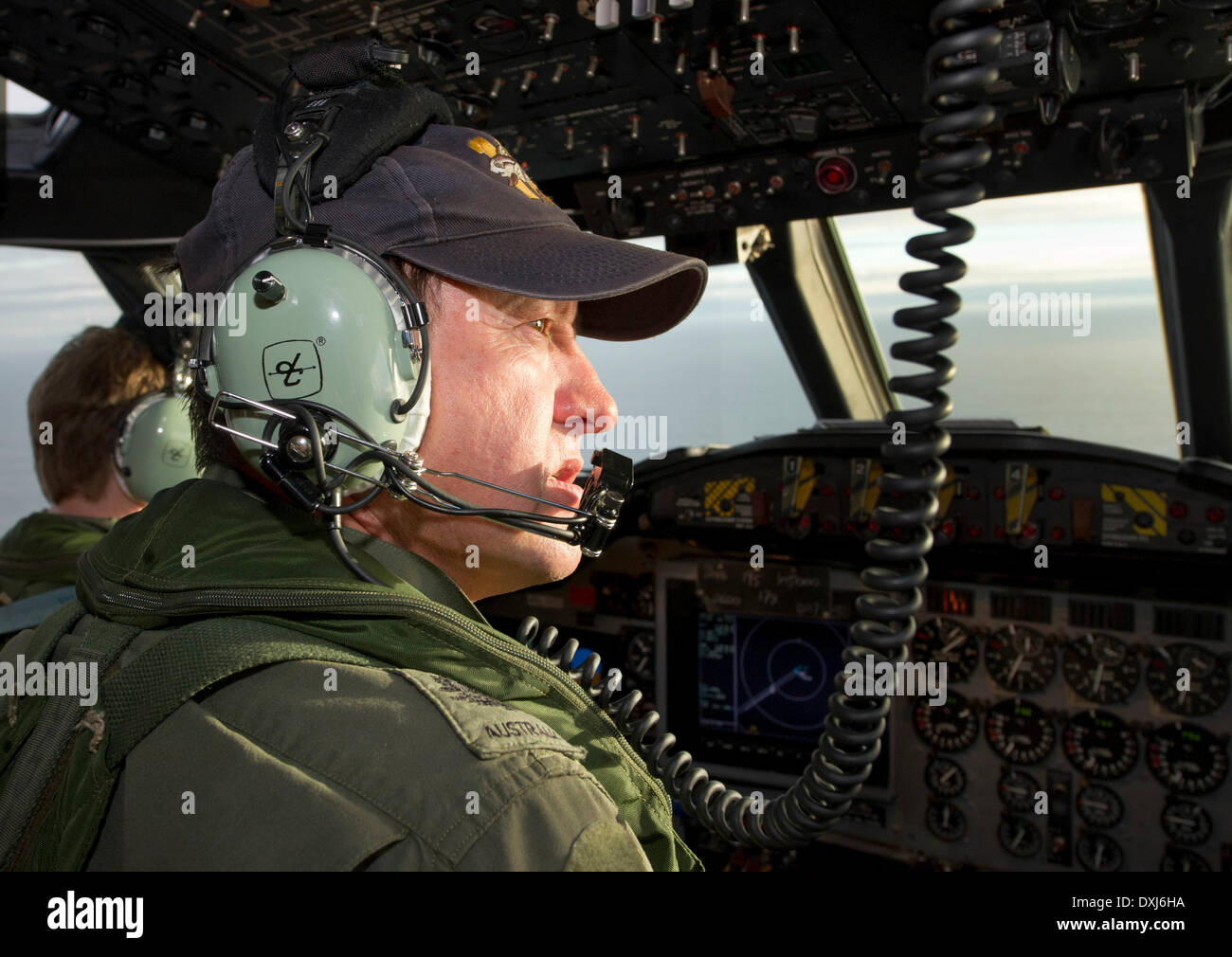 Canberra. 24th Mar, 2014. Royal Australian Air Force Warrant Officer Ron Day scans the ocean from the flight deck of an AP-3C Orion over the south Indian Ocean as part of the Australian Maritime Safety Authoirty-led search for Malaysia Airlines flight MH370 on March 24, 2014. © Australian Department of Defence/Xinhua/Alamy Live News - Stock Image