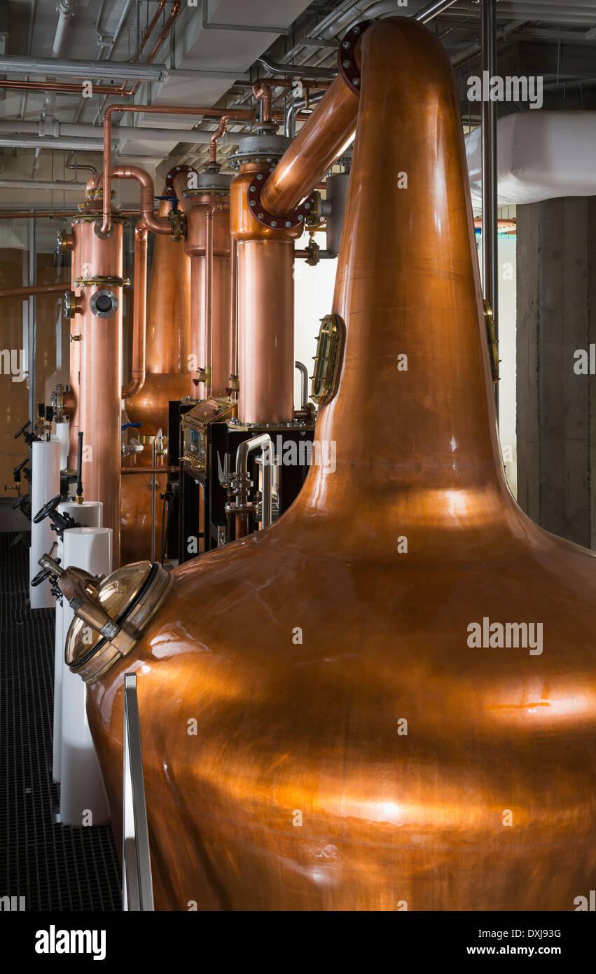Copper stills in distillery - Stock Image