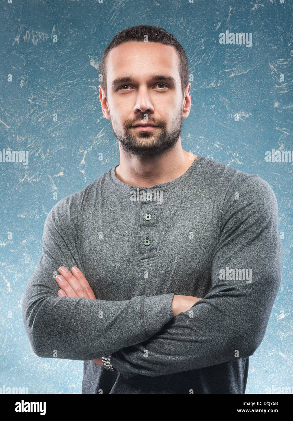 young handsome and athlet guy against a blue old wall - Stock Image