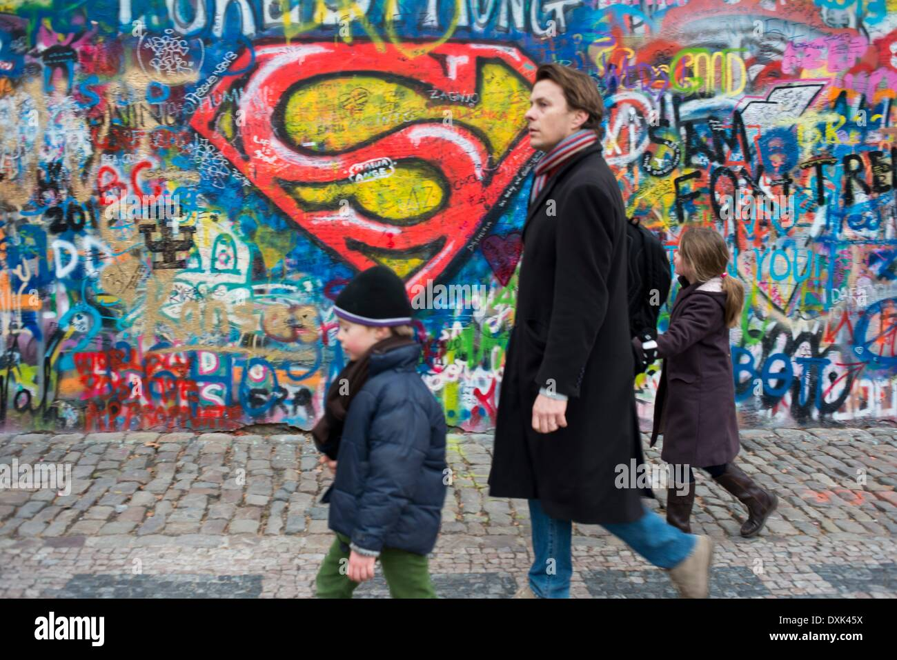 A girl walks past the John Lennon Wall in Prague center . The John Lennon Wall is a wall, which once was one most of which could be found in any of the buildings in the Mala Strana district in the capital of the Czech Republic. April 2013 - Stock Image