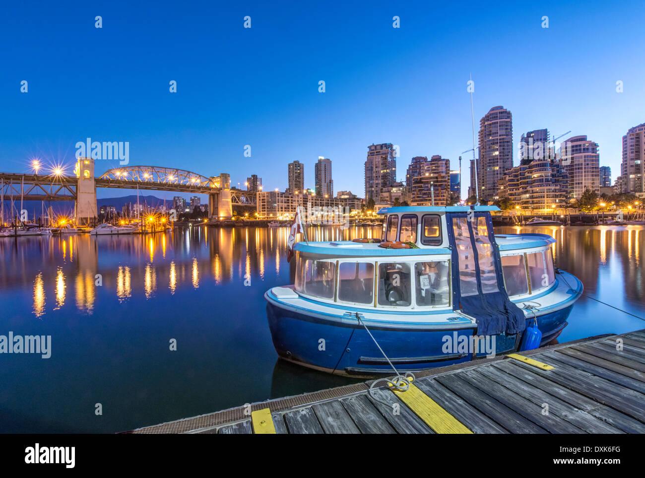 Waterfront skyline and harbor illuminated at night, Vancouver, British Columbia, Canada - Stock Image