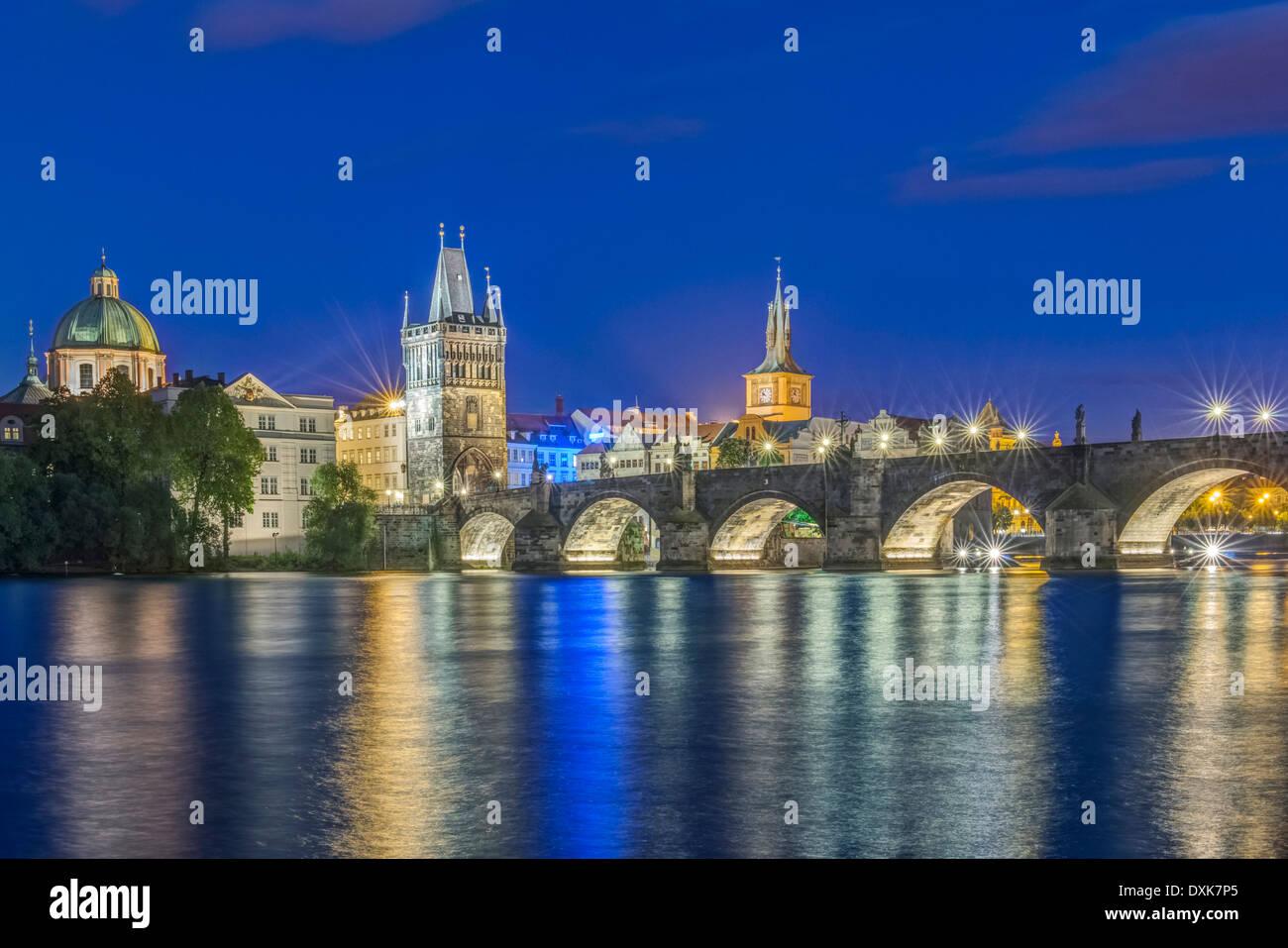Charles Bridge and city illuminated at night, Prague, Czech Republic - Stock Image