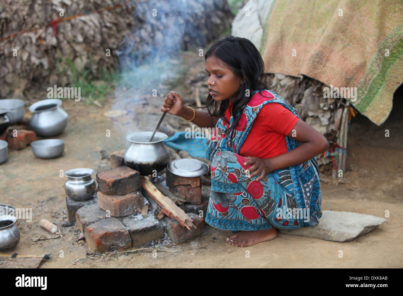 Tribal woman cooking food on hearth. Musahar or Bhuija tribe. Keredari village and block, District Hazaribaug, Jharkhand, India. - Stock Image
