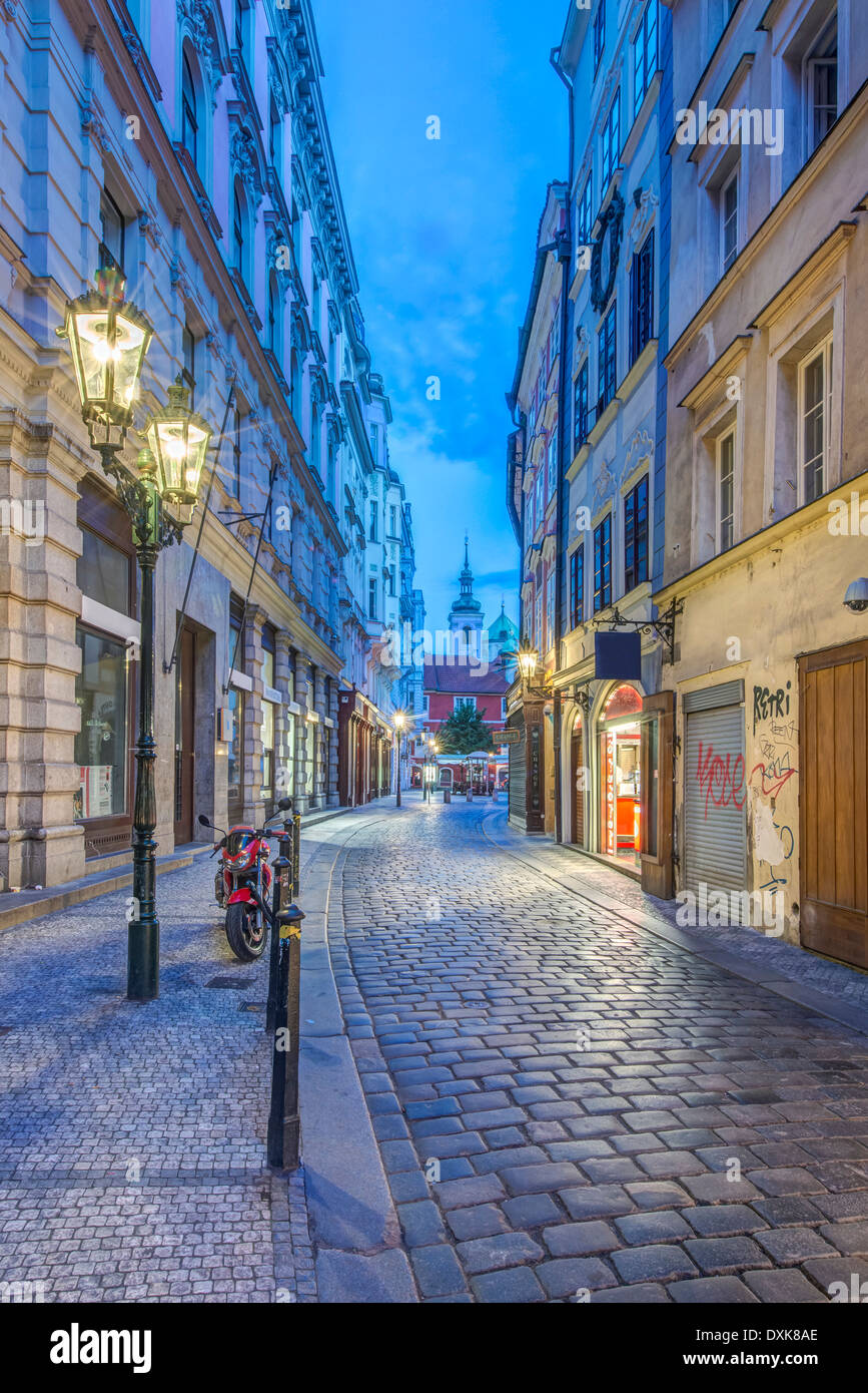 Illuminated streetlamp on cobblestone alley at dawn, Prague, Central Bohemia, Czech Republic - Stock Image