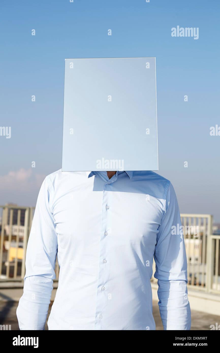 Man's face hidden behind light blue rectangle - Stock Image