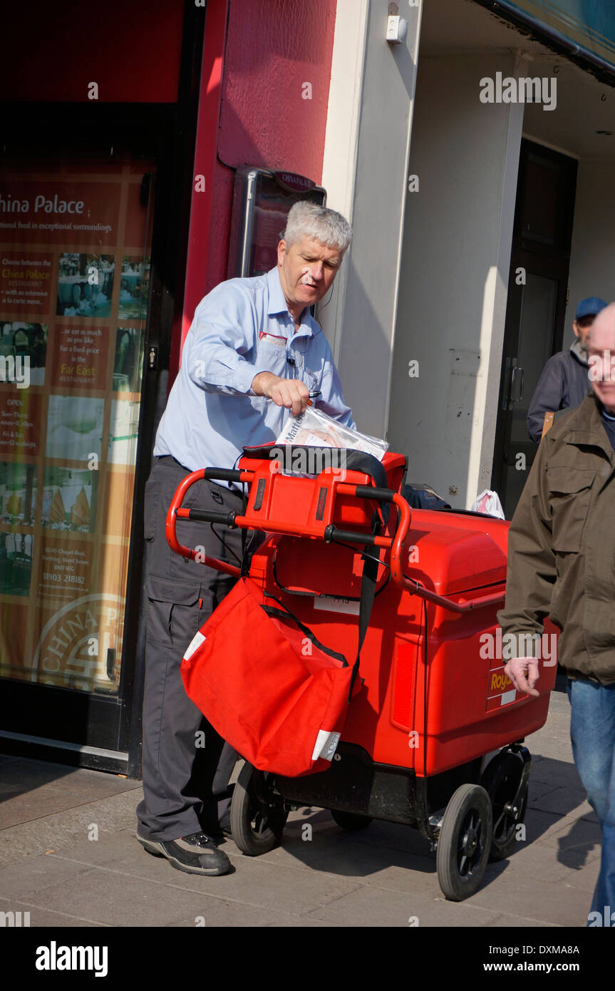 Postman on his round delivering letters & parcels using a 'high capacity' trolley (replacing the old fashioned bicycle) - Stock Image