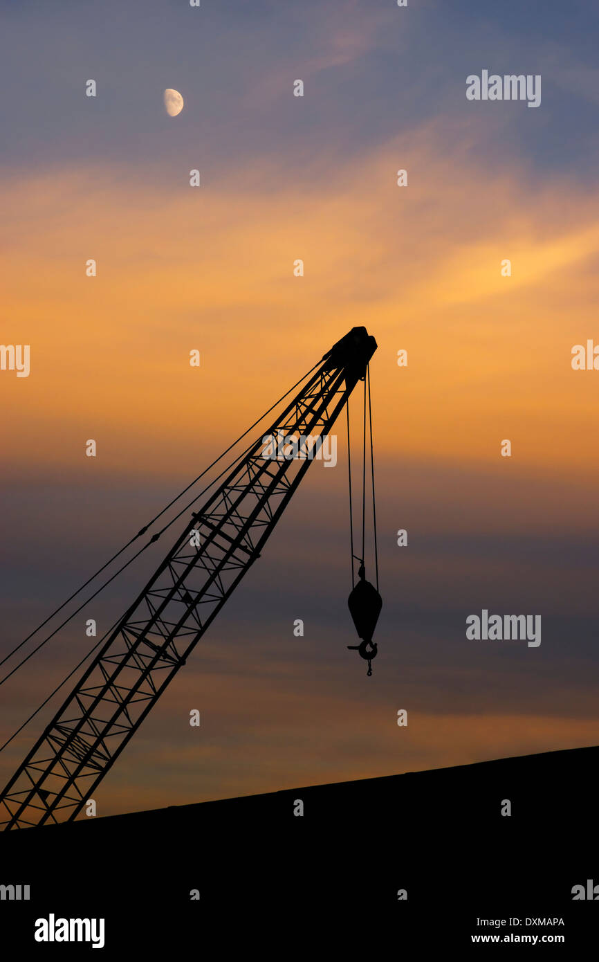 A crane derrick over industrial buildings against a dramatic evening sky; industry or cargo handling concept - Stock Image