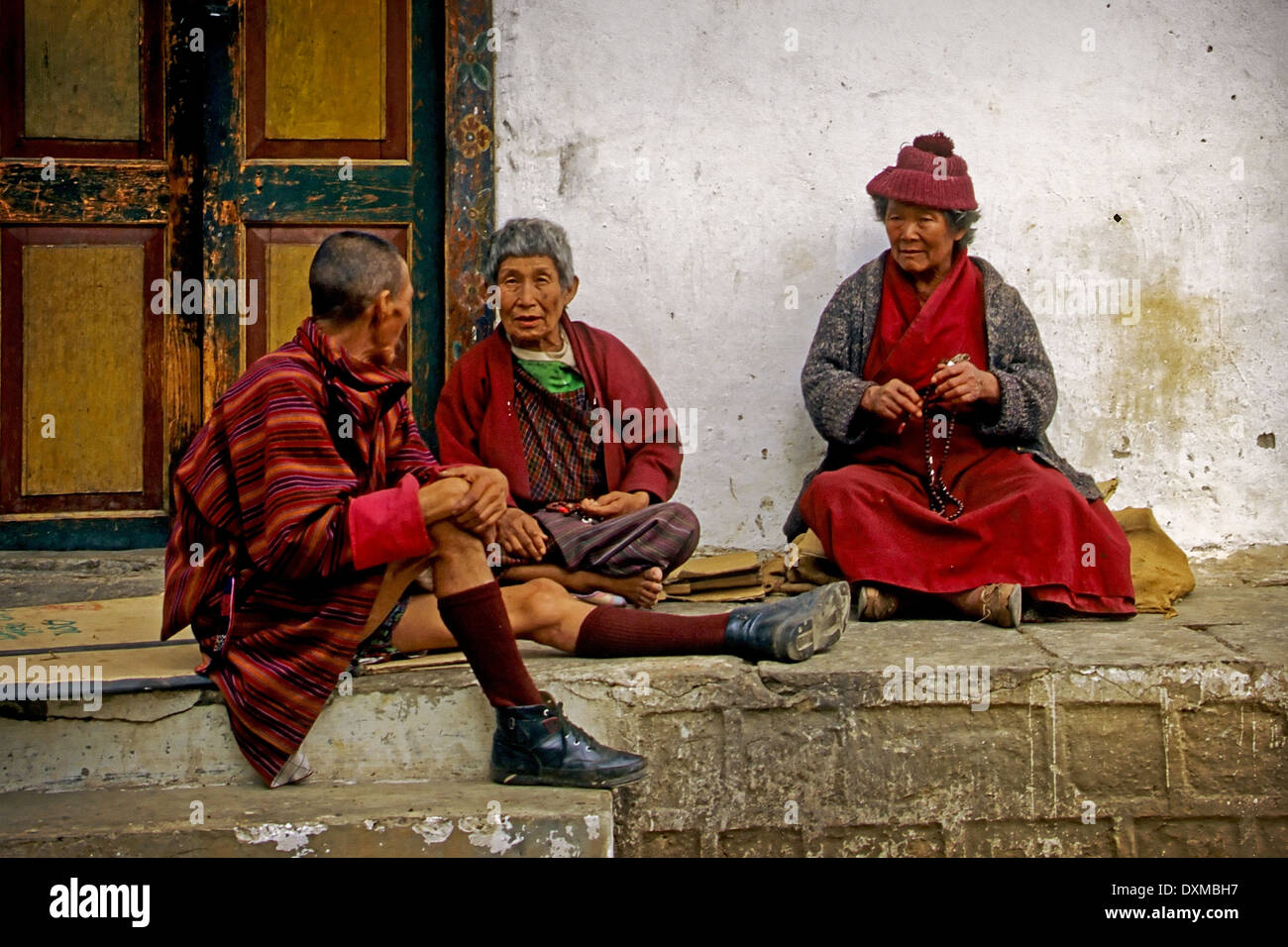 Bhutanese people in traditional costume in conversation in Thimpu, Bhutan. Digitally Manipulated Image. - Stock Image