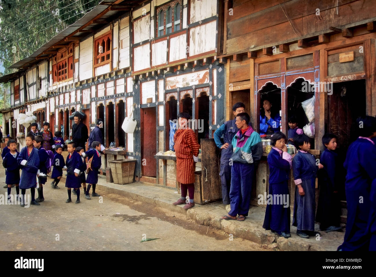 Bhutanese school children and people in national dress in fornt of traditional buildings in Wangde Phodrung, Bhutan. - Stock Image