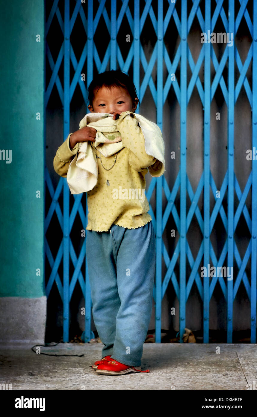 Bhuitanese child in the street. Digitally Manipulated Image. Stylised by sharpening and enhancing color. - Stock Image