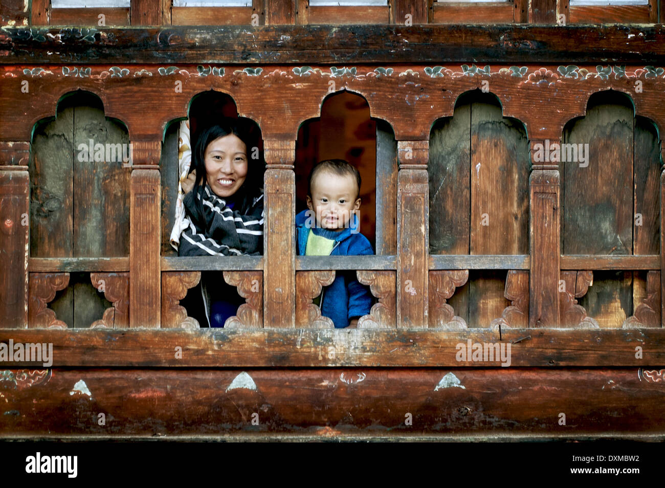 Bhutanese woman and child in window in Paro, Bhutan. Digitally Manipulated Image. Stylised by sharpening and enhancing color. - Stock Image