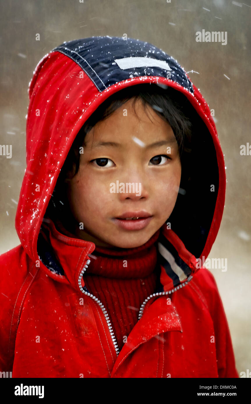 Bhutanese child in falling snow in Gangtey, Bhutan. Digitally Manipulated Image. Stylised by sharpening and enhancing color - Stock Image
