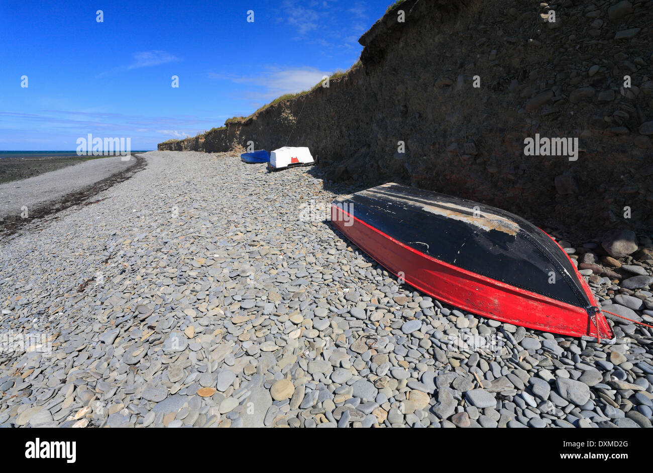 Boats under a small cliff on Llanon beach, Ceredigion, Wales. - Stock Image