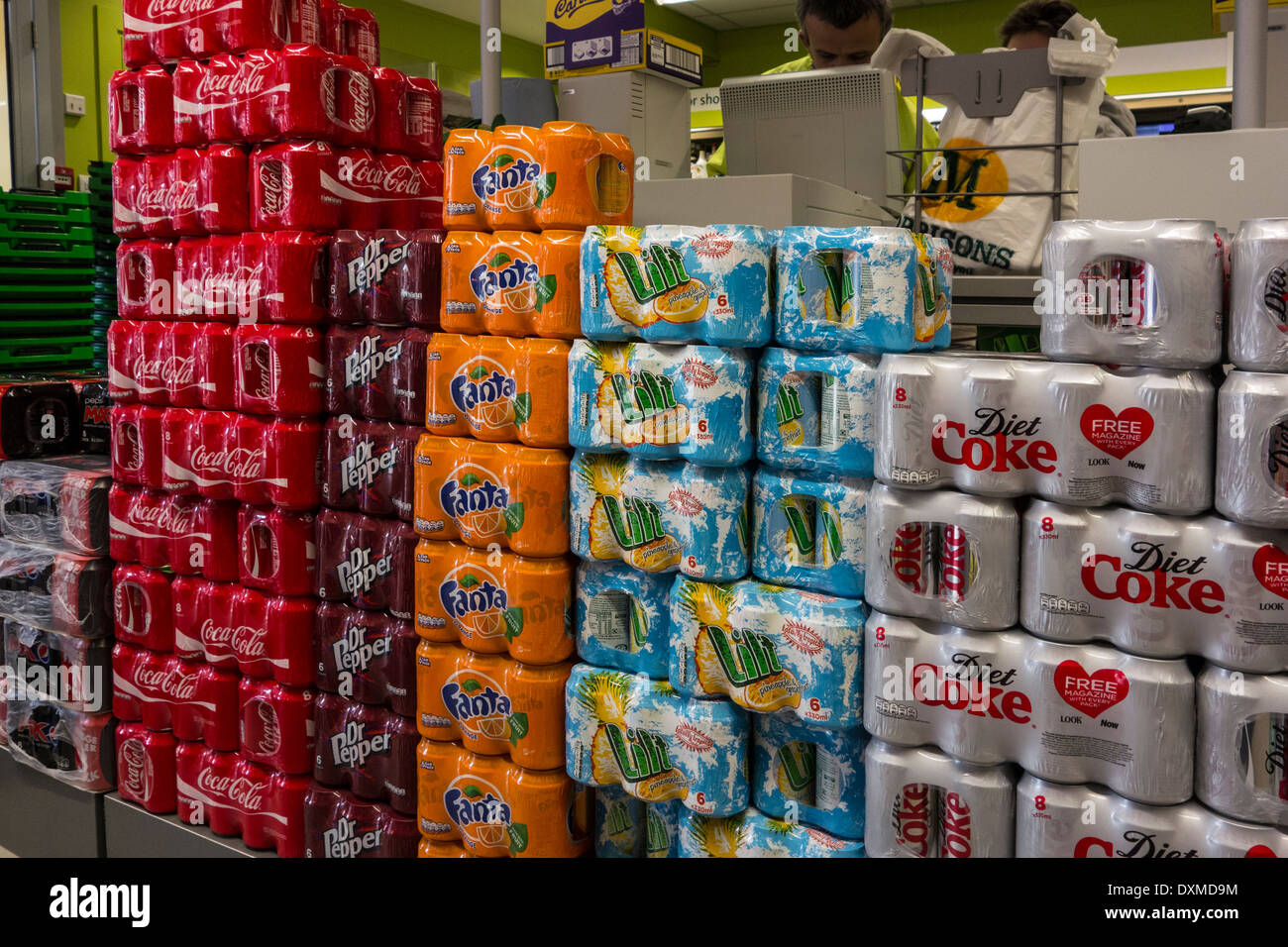 Cans of soft drinks piled high in a supermarket. - Stock Image