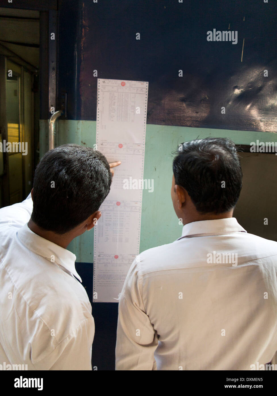 India, Rail Travel, Jammu Railway Station, two men checking reservations list pasted to side of train - Stock Image