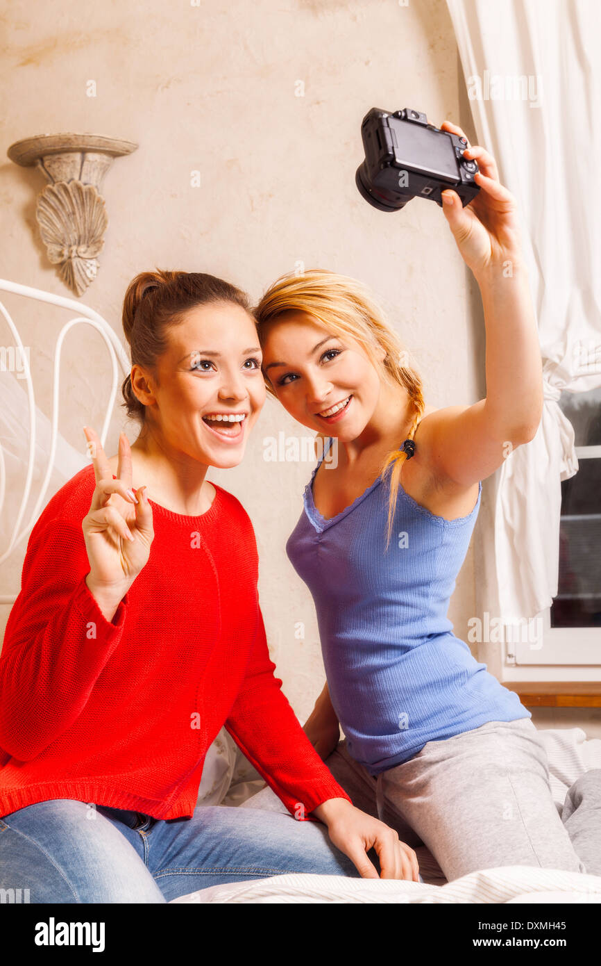 Two girls doing themselves photo in a bedroom Stock Photo