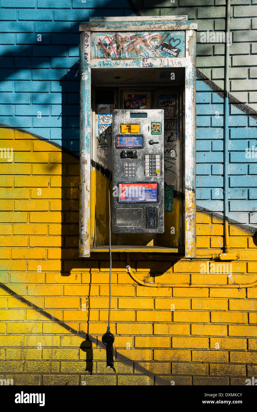 Sign of the times. Broken phone dangling from pay phone kiosk. - Stock Image