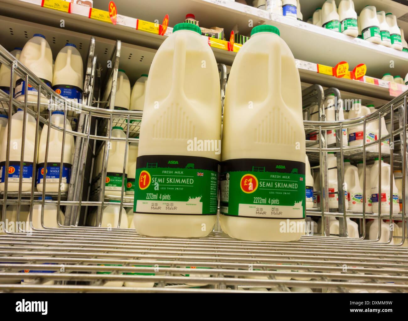 Milk in supermarket trolley in Asda store. UK - Stock Image