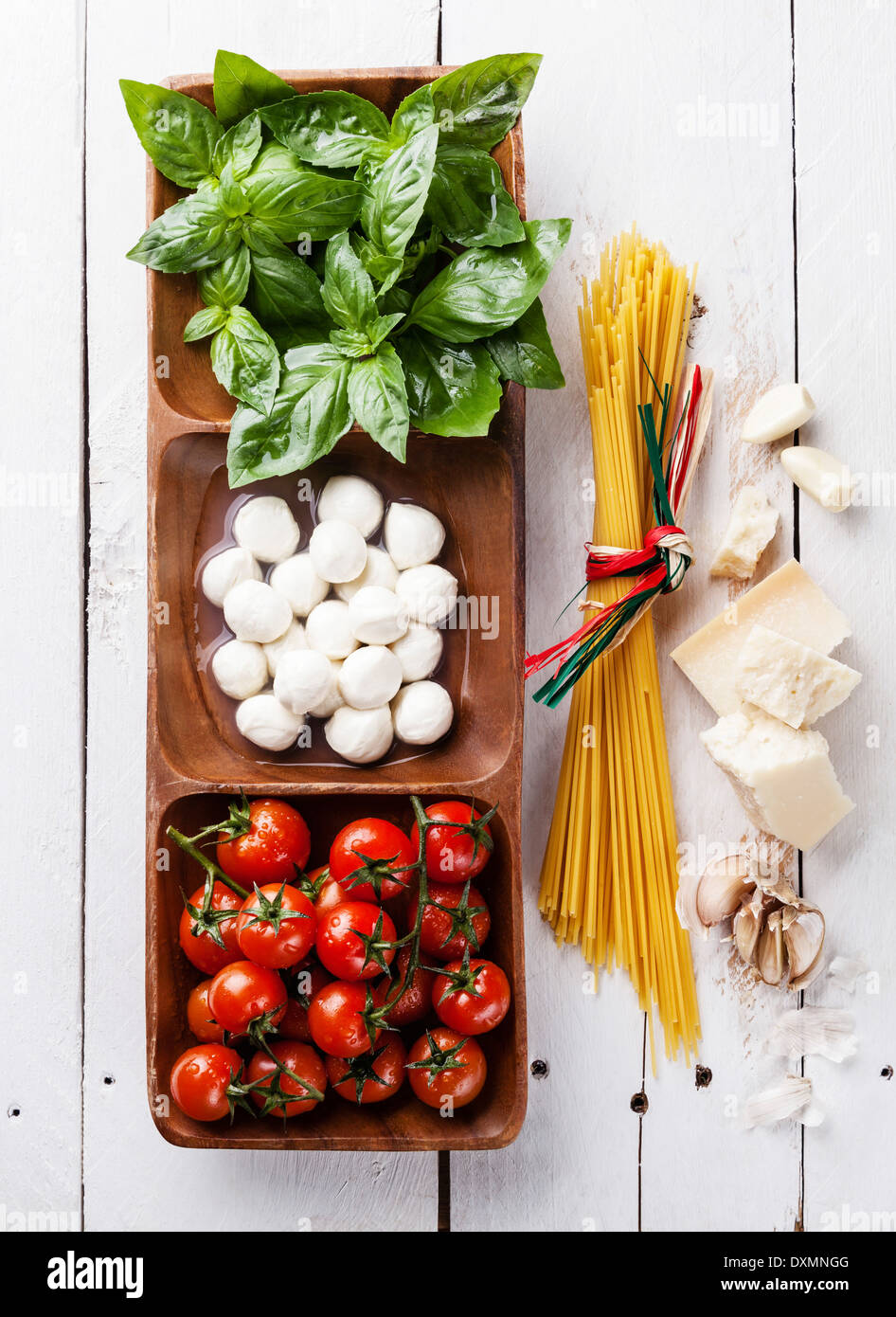 Italian flag colors with Green basil, white mozzarella, red tomatoes, parmesan and spaghetti - Stock Image