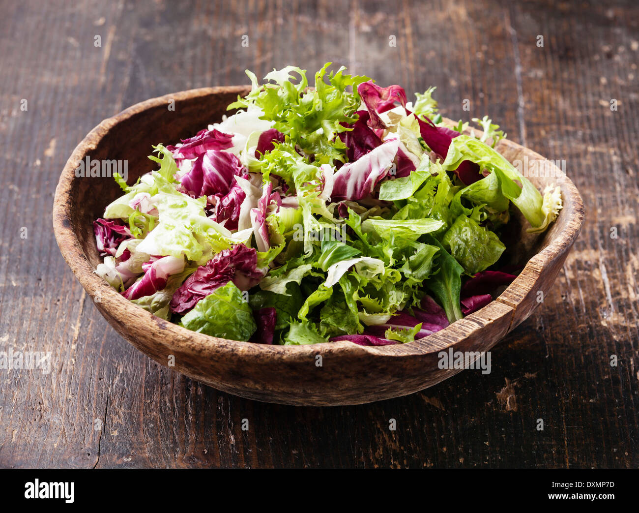 Fresh salad leaves mix in wooden bowl - Stock Image