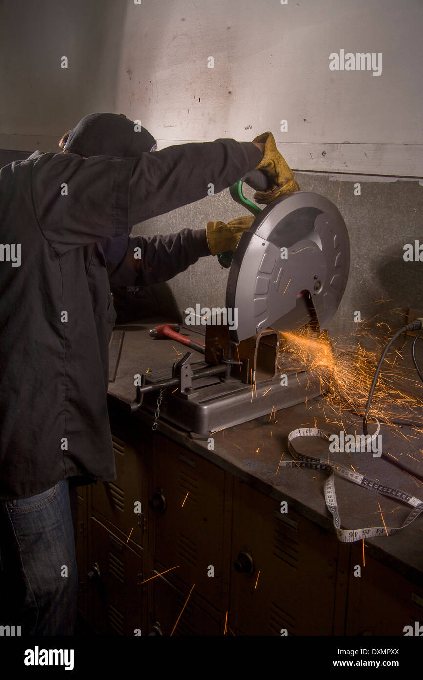 Sparks fly as a high school student uses a circular saw to cut a metal pipe in auto shop class in San Clemente, Stock Photo