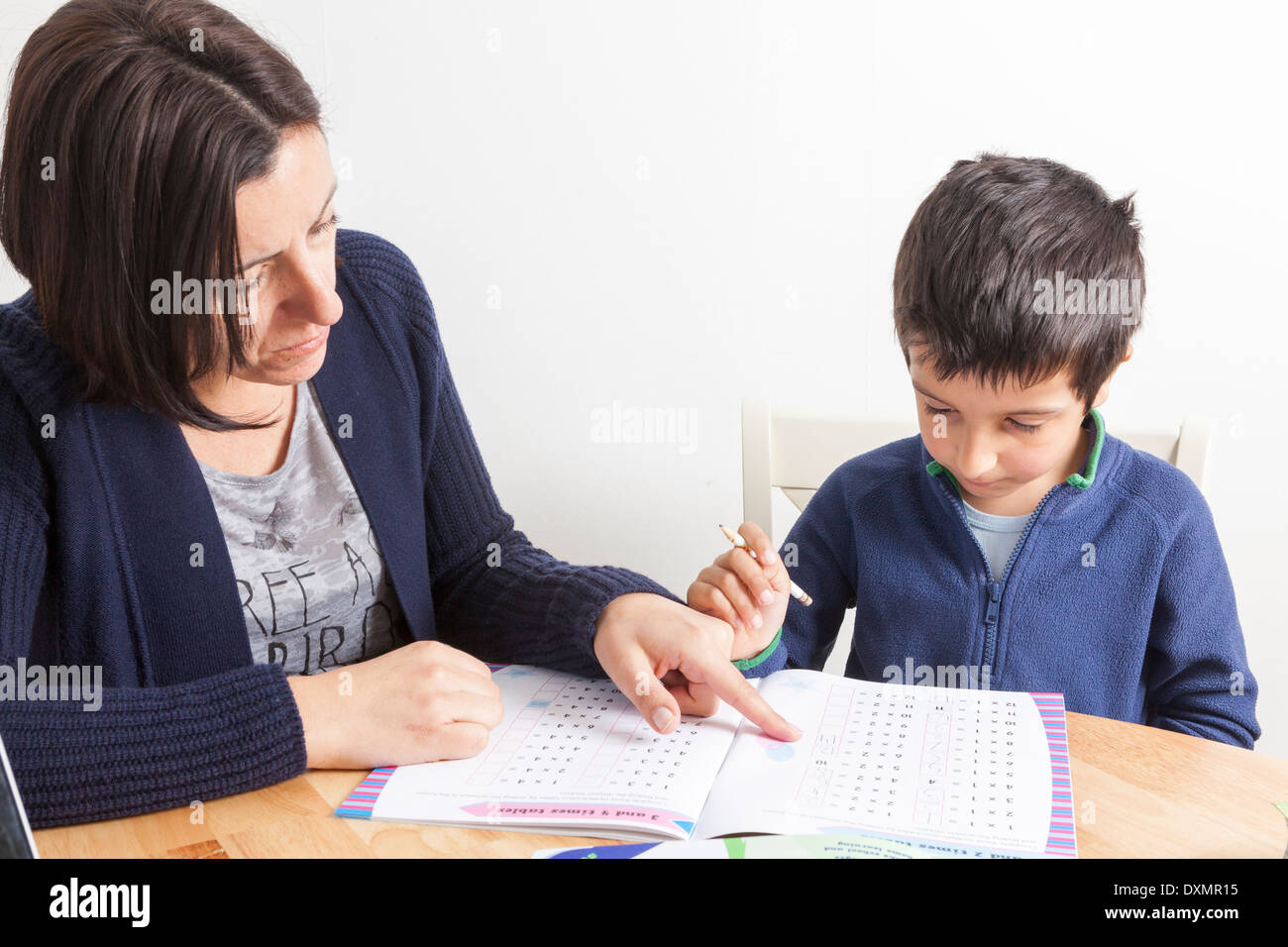 Parent tutoring young boy at home - Stock Image
