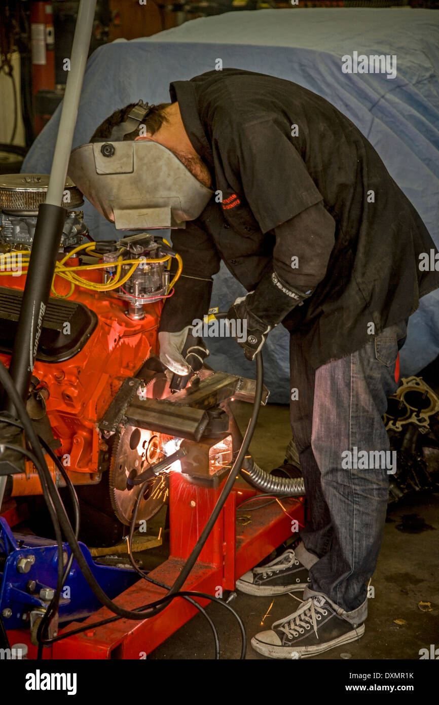 A teen boy arc welds an engine support in a high school auto shop class in San Clemente, CA, Stock Photo