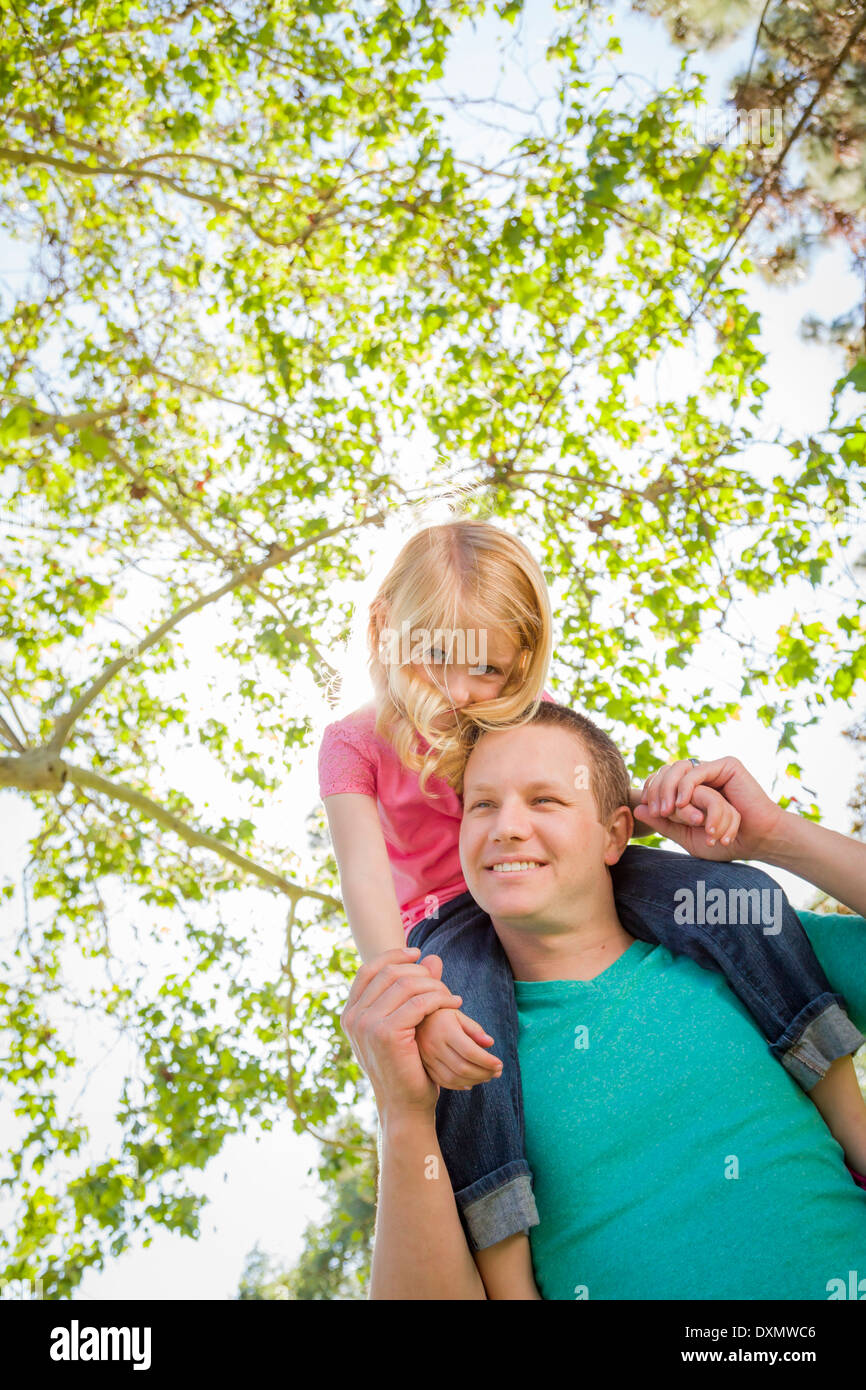 Cute Young Girl Rides Piggyback On Her Dads Shoulders Outside at the Park. - Stock Image