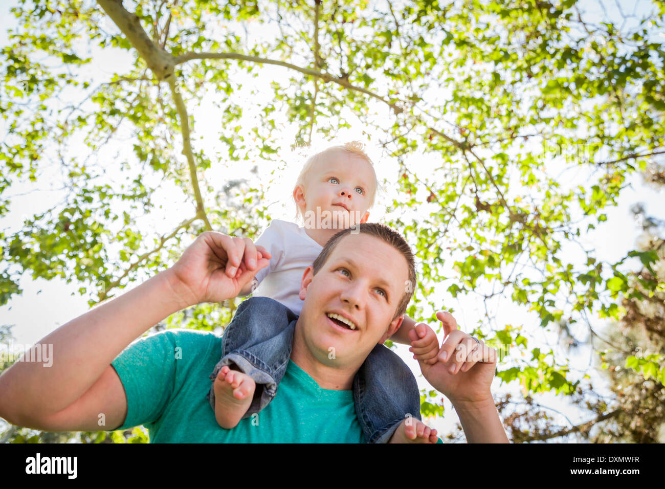 Cute Young Boy Rides Piggyback On His Dads Shoulders Outside at the Park. - Stock Image