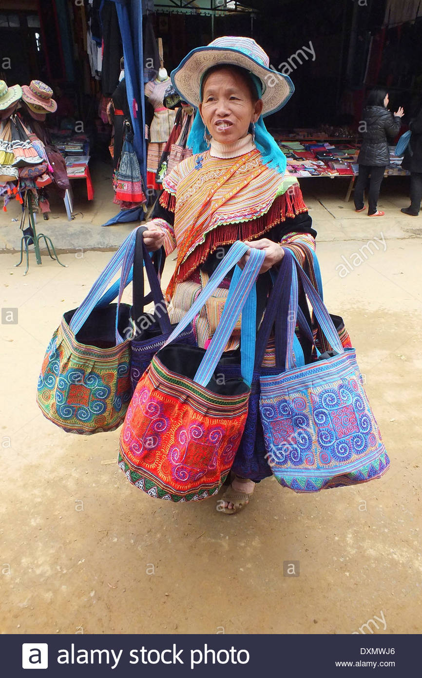 Vietnam Bac Ha Market Tribeswoman in traditional dress with bags - Stock Image