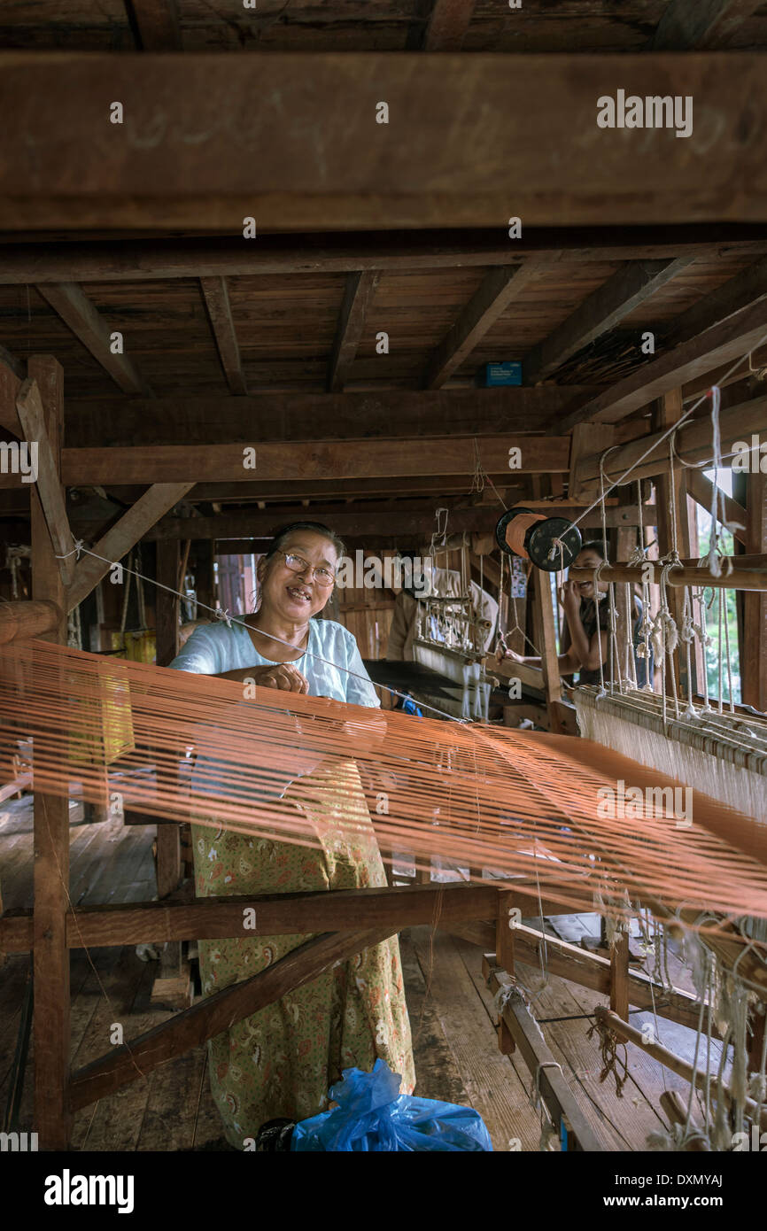 Woman setting up the warp threads on a hand loom, Inle Lake, Myanmar - Stock Image