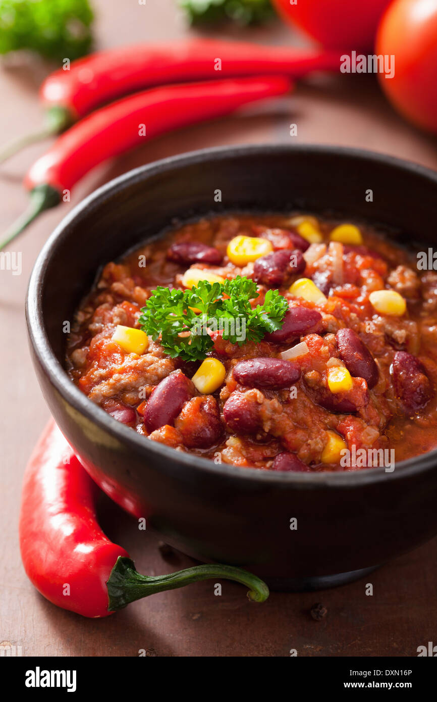 mexican chili con carne in black plate with ingredients - Stock Image