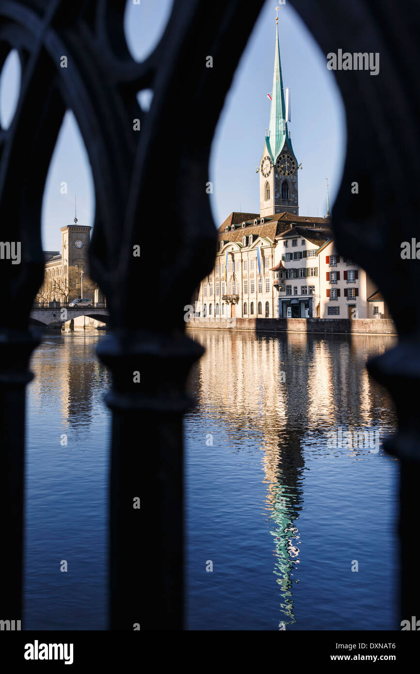 The Fraumünster church, reflected on the Limmat river, seen through the railing. Zürich, Switzerland. - Stock Image