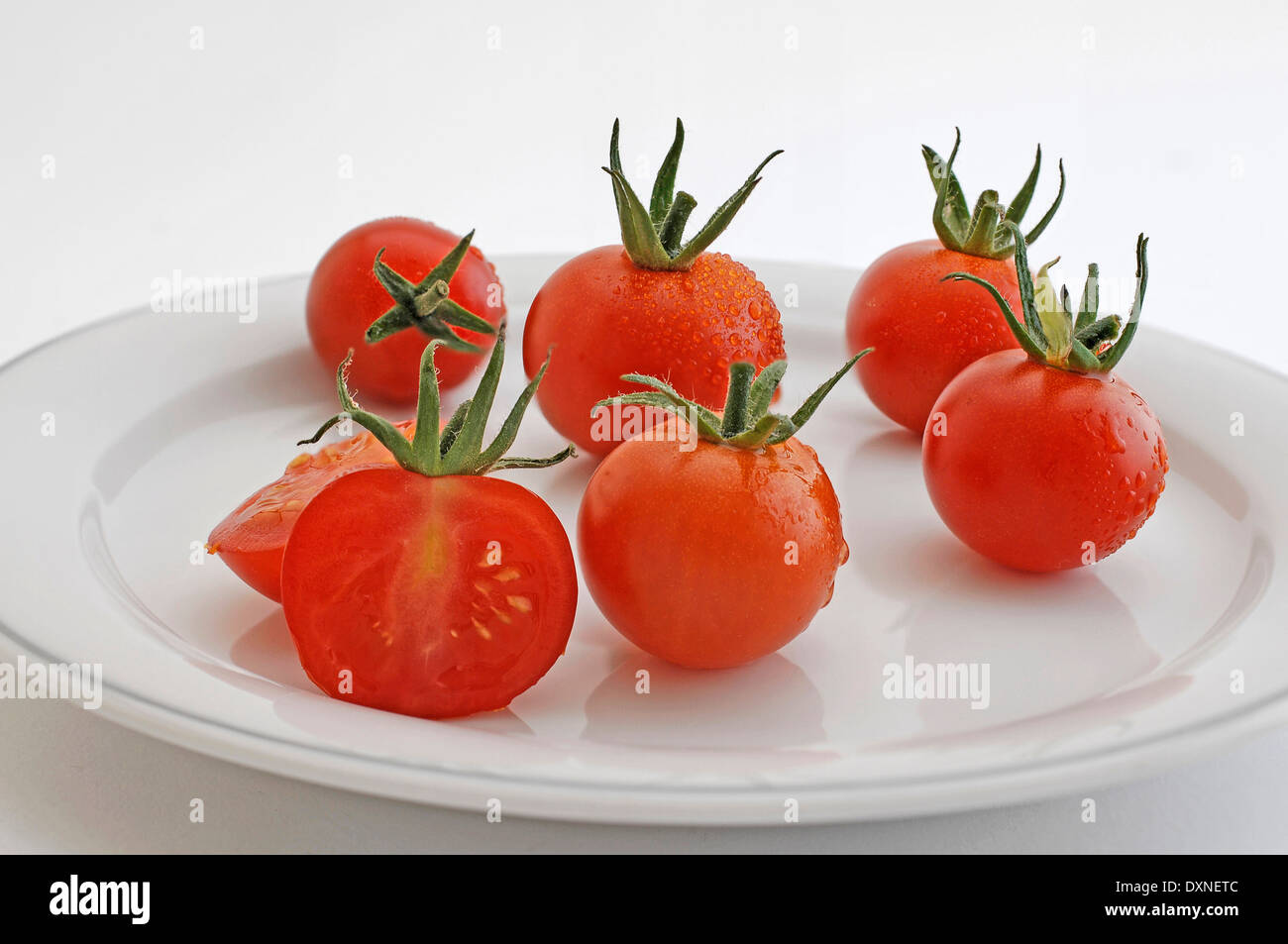 tomato on a white plate - Stock Image