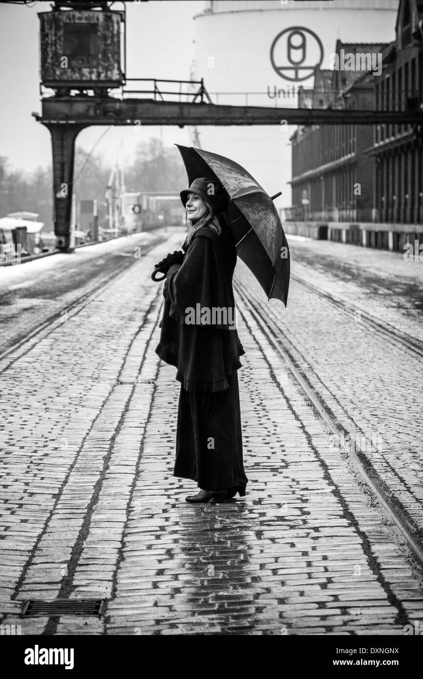 Germany, Berlin, woman with umbrella watching buildings at industrial harbour - Stock Image
