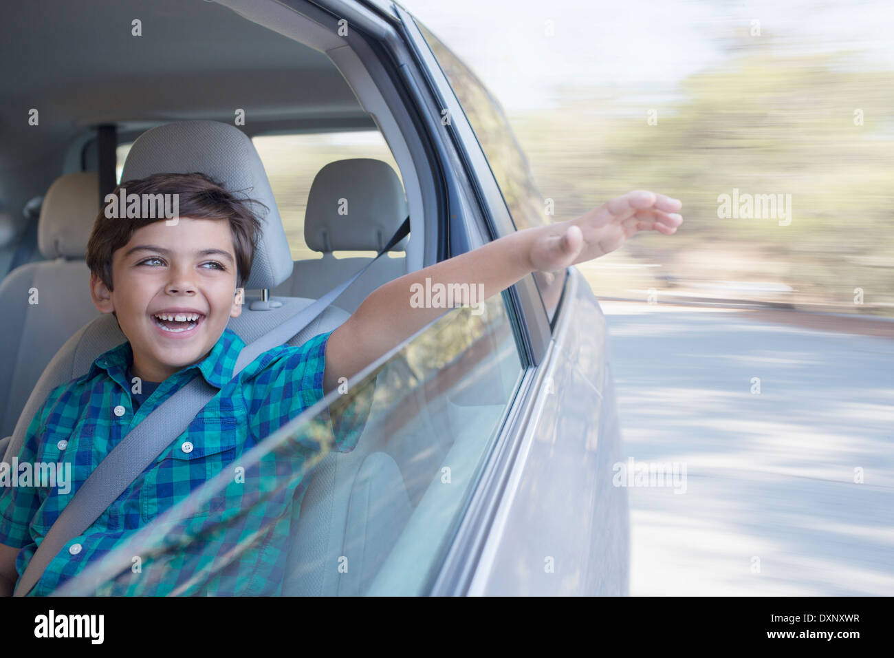 Happy boy sticking hand out window of car - Stock Image