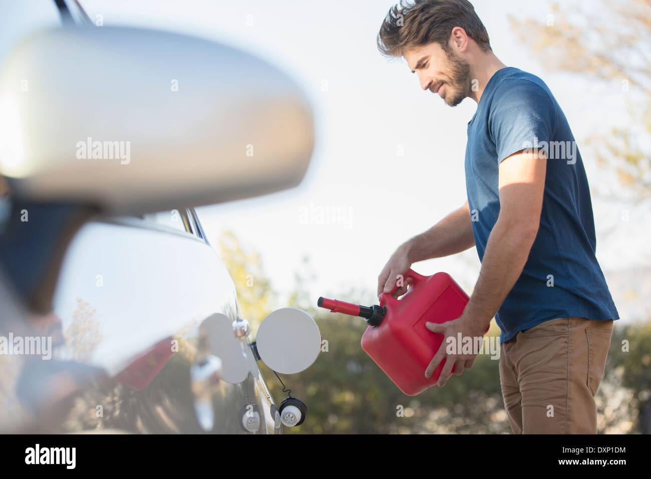 Man filling gas tank at roadside - Stock Image