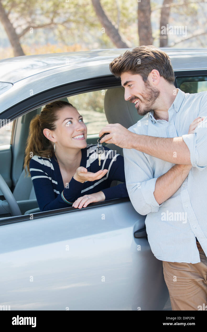 Man giving woman in car keys - Stock Image