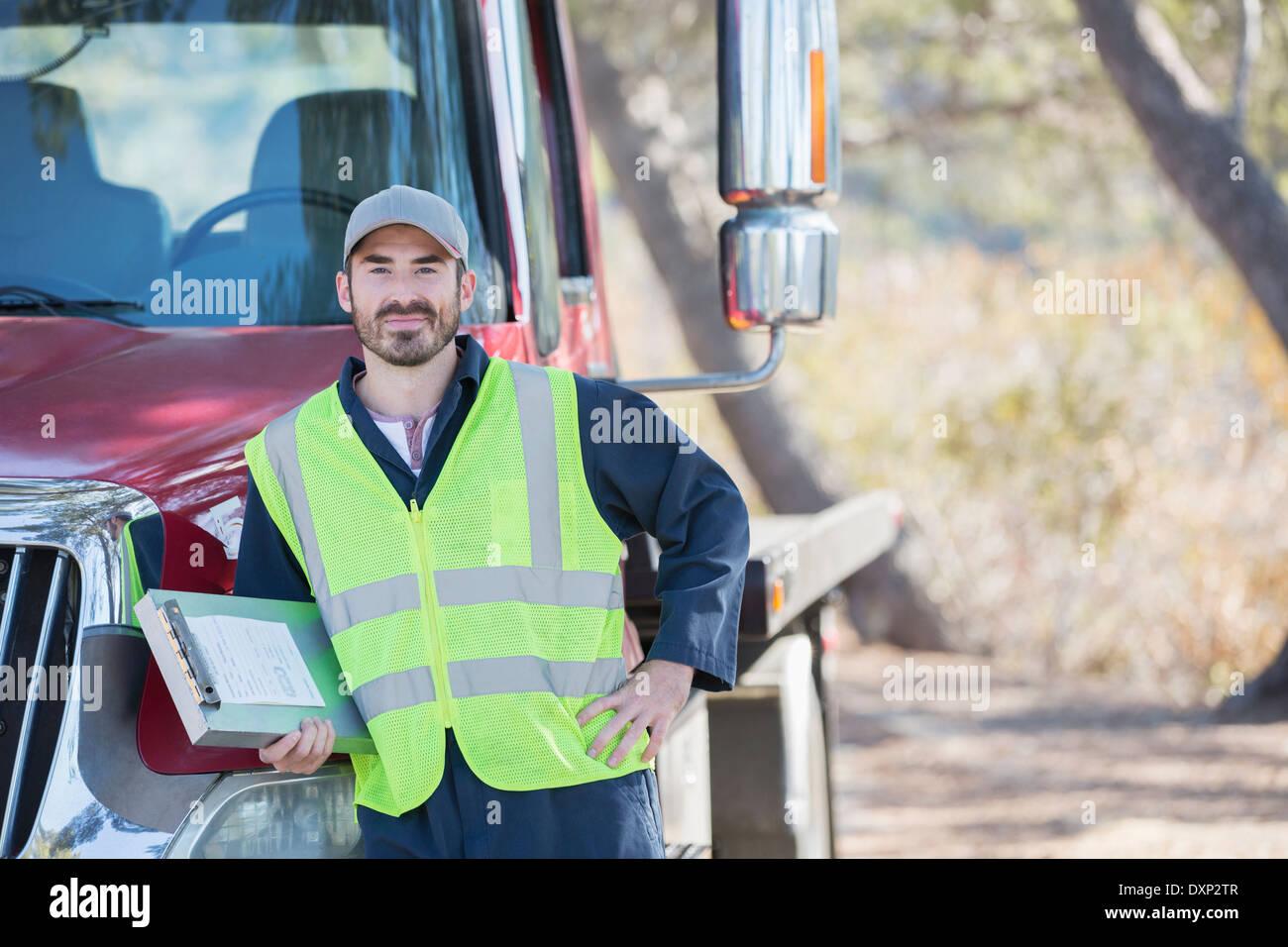 Portrait of confident roadside mechanic leaning on truck Stock Photo