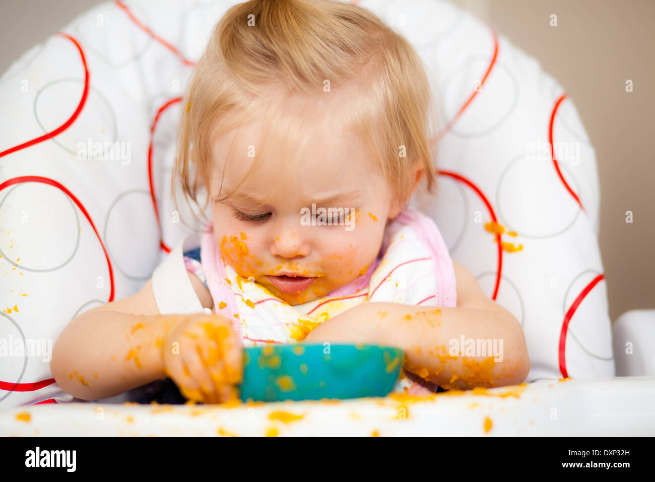 Little girl having a messy lunch - Stock Image