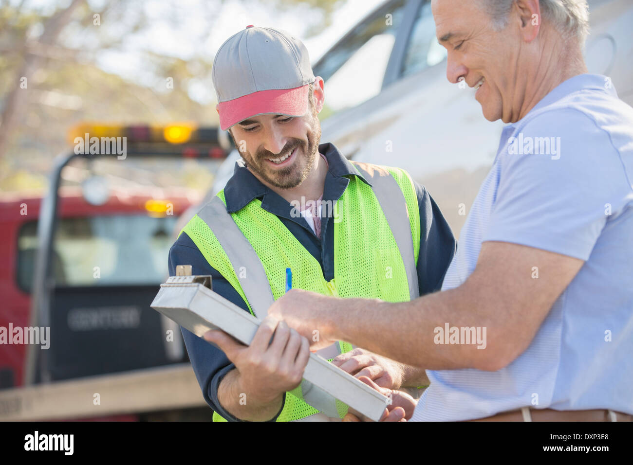Man signing paperwork for roadside mechanic Stock Photo