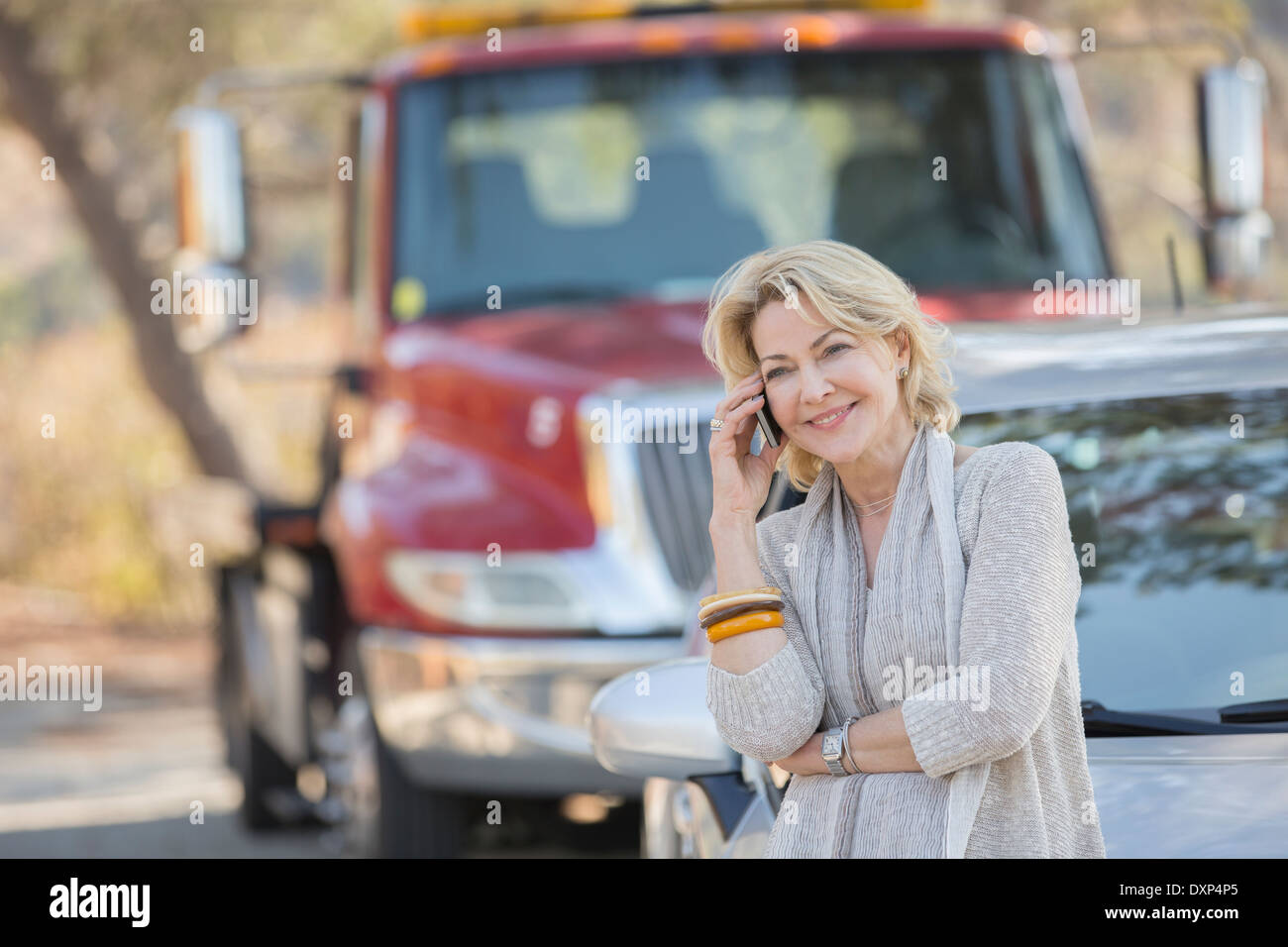 Woman talking on cell phone near tow truck at roadside - Stock Image