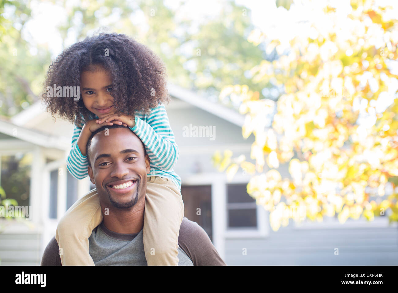 Portrait of happy father carrying daughter on shoulders - Stock Image