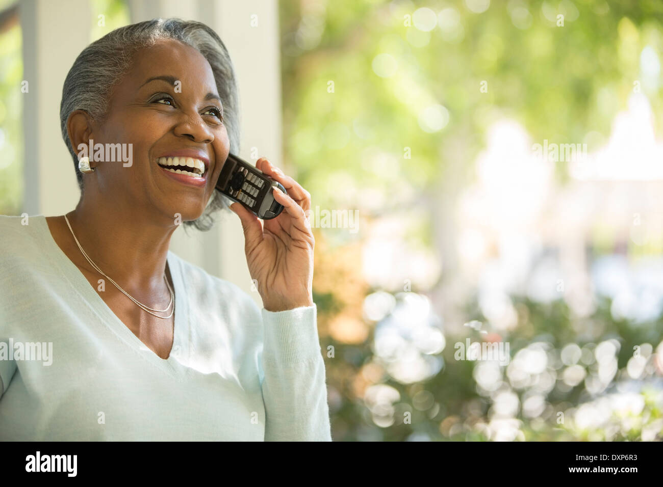 Happy senior woman talking on telephone outdoors - Stock Image