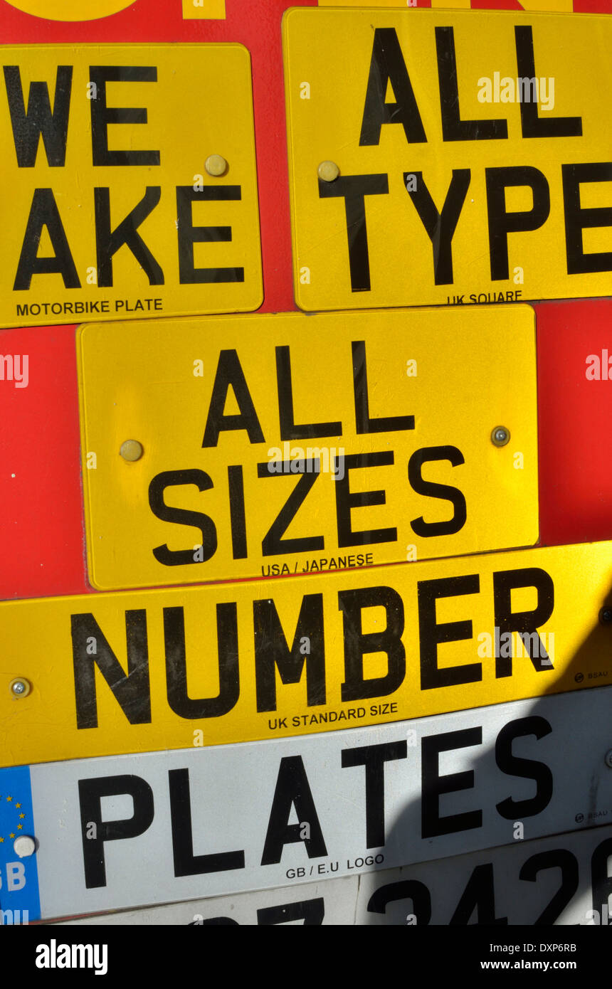 Shop window display advertising different types of car number plates - Stock Image