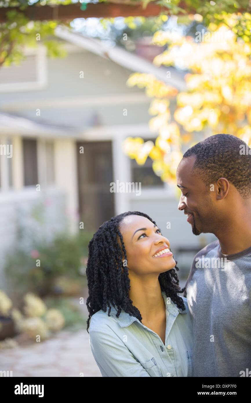 Happy couple hugging outside house - Stock Image