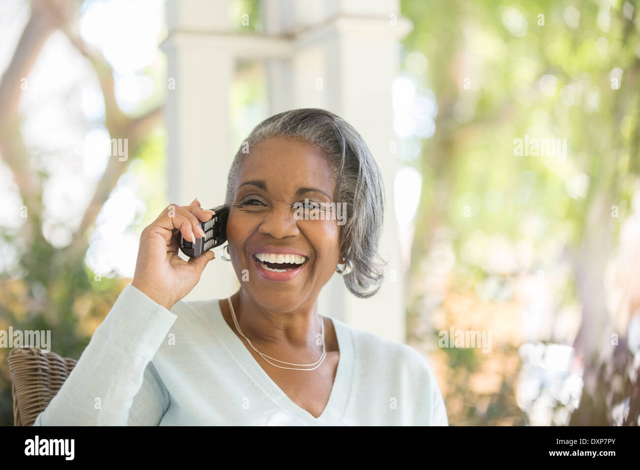 Enthusiastic senior woman talking on telephone on porch - Stock Image