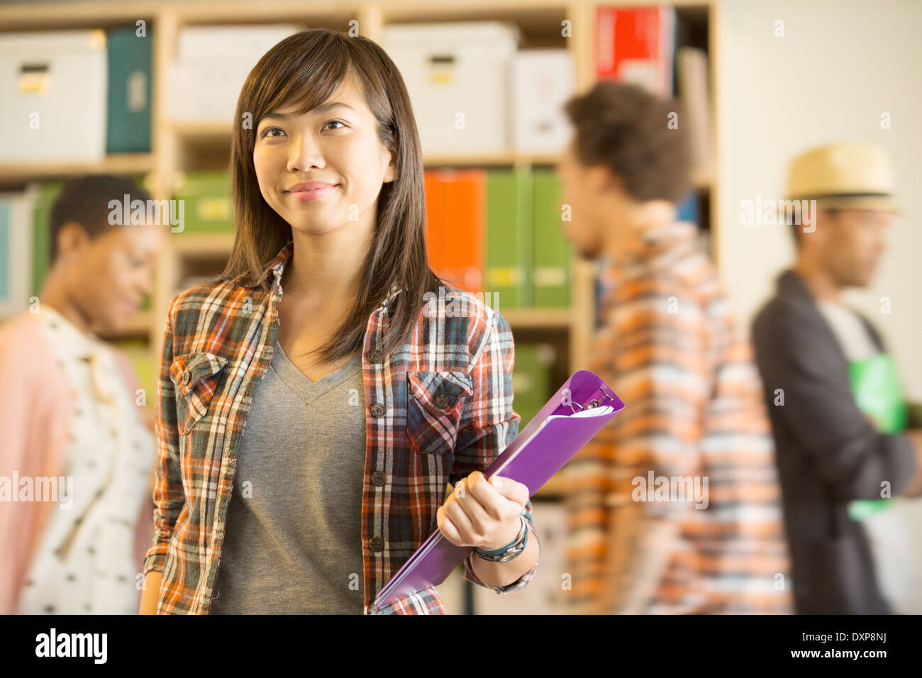 Portrait of confident casual businesswoman with co-workers passing in background - Stock Image