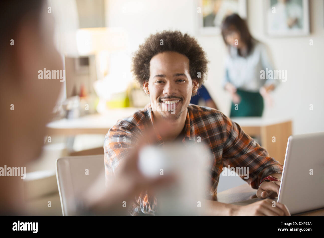 Happy creative businessman using laptop in meeting - Stock Image